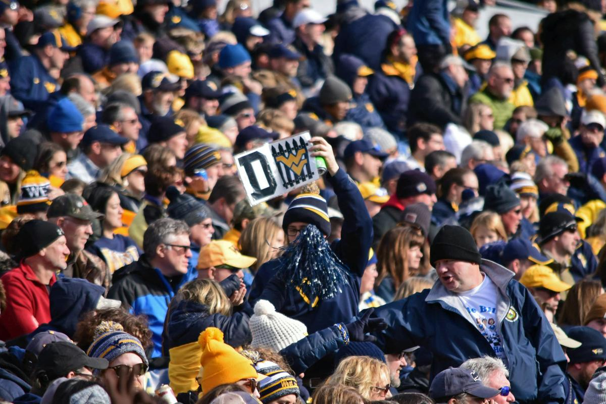 """WVU fans hold up a """"defense"""" sign above the crowd."""