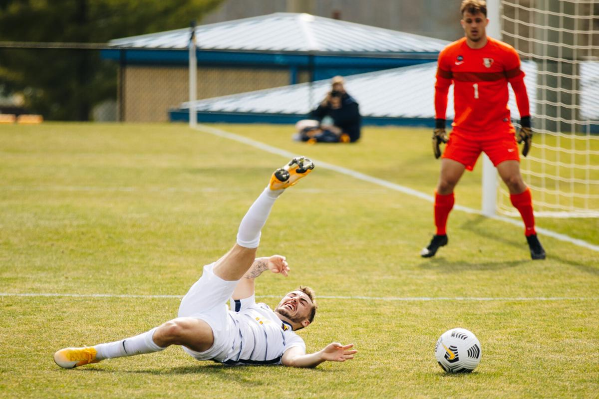 West Virginia University midfielder Luke McCormick falls during a match at Dick Dlesk Stadium on March 17, 2021.