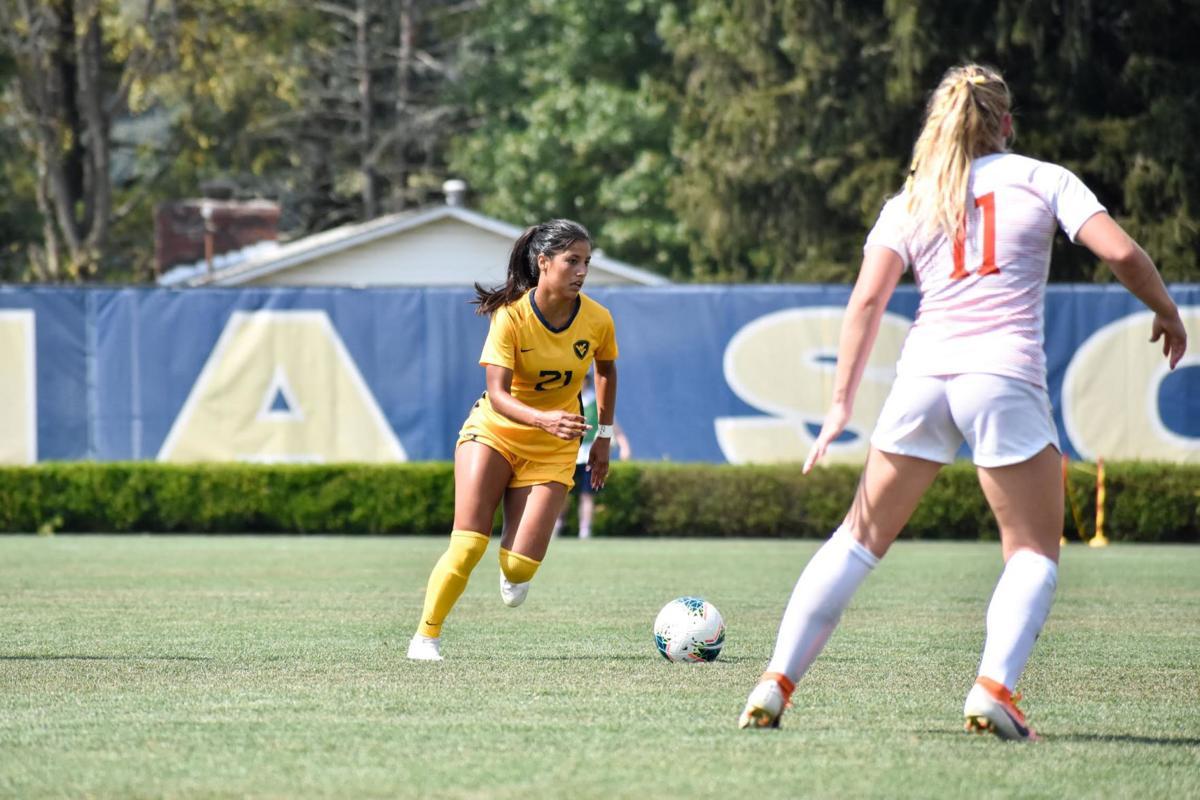 A WVU women's soccer player dribbles the ball down the field.