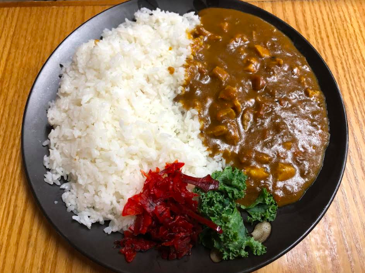 A picture of chicken curry. There's a pile of rice on one side of the pic and a brown pile of curry on the other side.