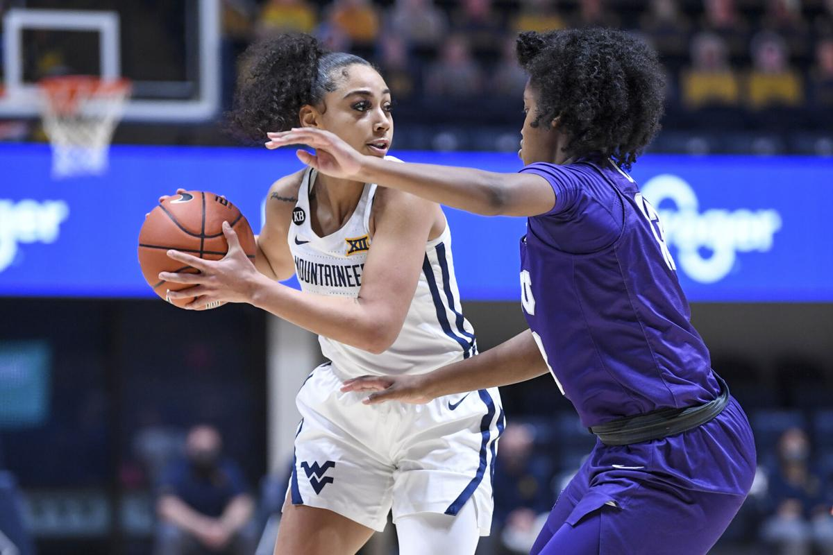 WVU guard Kysre Gondrezick looks for an open teammate against the TCU Horned Frogs at the WVU Coliseum on Feb. 20, 2021.