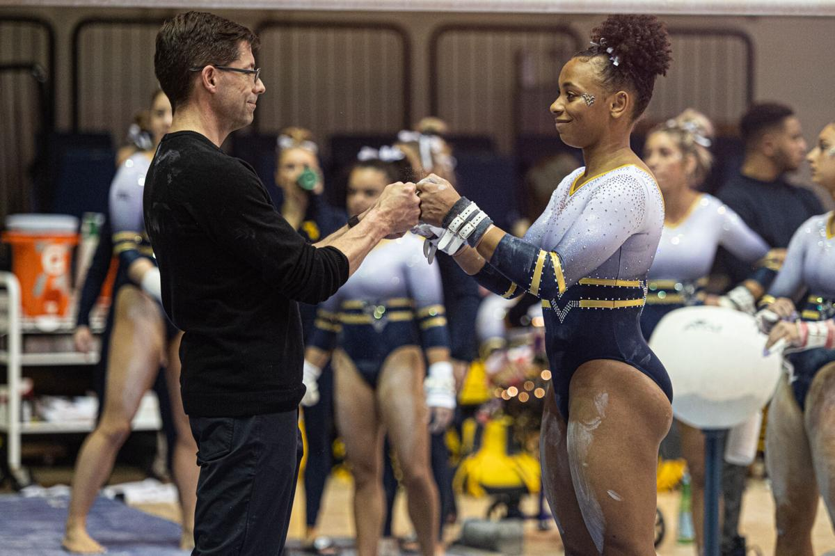 Feb. 23, 2020. Sophomore Kendra Combs fist bumps head coach Jason Butts before her bars routine.