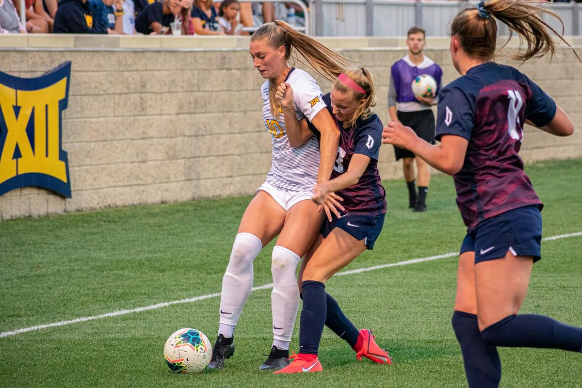 WVU defender Jordan Brewster fights for the ball with a Duquesne soccer player.