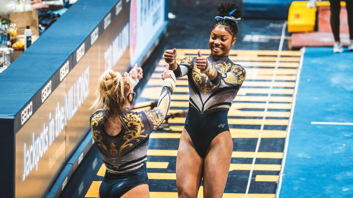 West Virginia gymnast Kiana Lewis celebrates with fellow teammate during a WVU gymnastics meet.