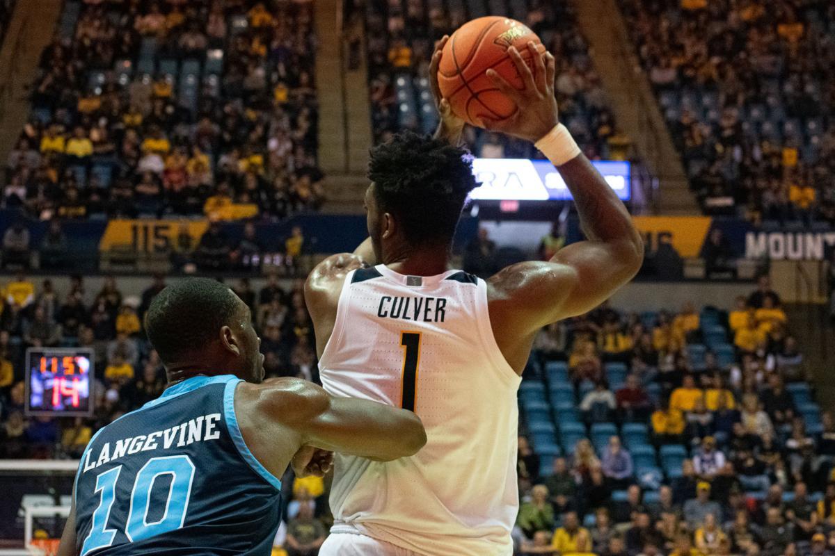 West Virginia forward Derek Culver searches for an open teammate against Rhode Island