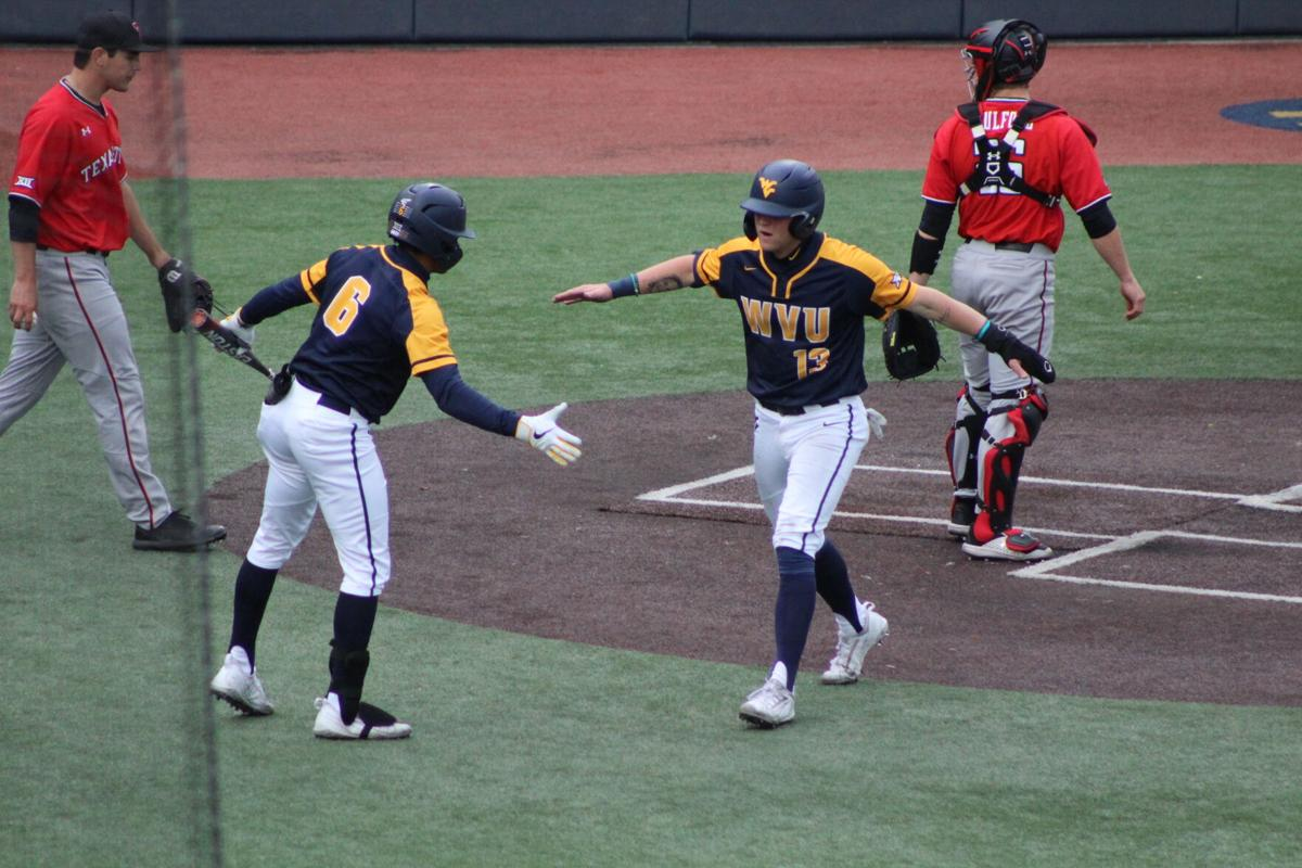West Virginia's Victor Scott (6) and Kevin Brophy (13) high-five during a game against Texas Tech on April 17, 2021, in Morgantown.