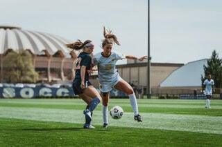 West Virginia midfielder Lily McCarthy dribbles the ball against a Virginia defender on April 3, 2021, in Morgantown, W.Va.