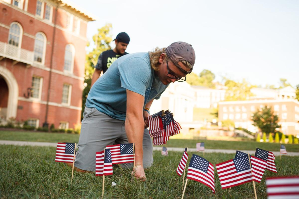 A student on his knees planting flags into grass.
