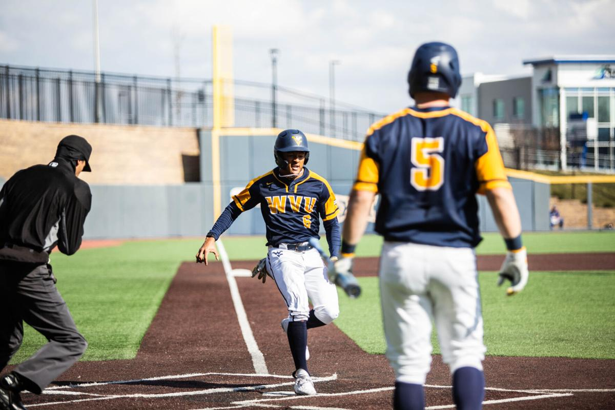 Sophomore outfielder Victor Scott (6) crosses home plate in a win over Morehead State at the Monongalia County Ballpark in Morgantown, W.Va., on March 16 2021.