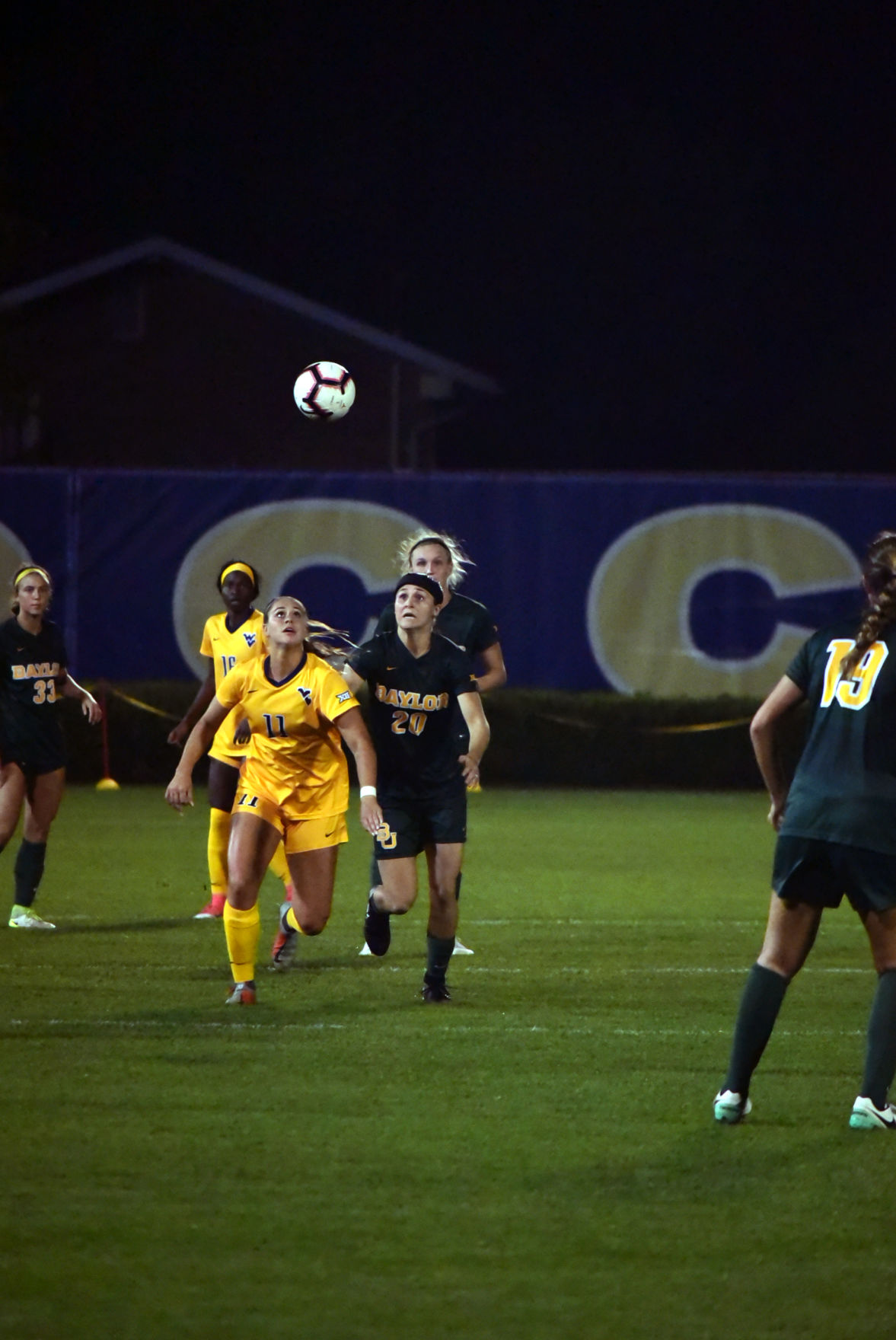WVU midfielder Addison Clark eyes the ball as she competes with Baylor midfielder Julie James to get there.