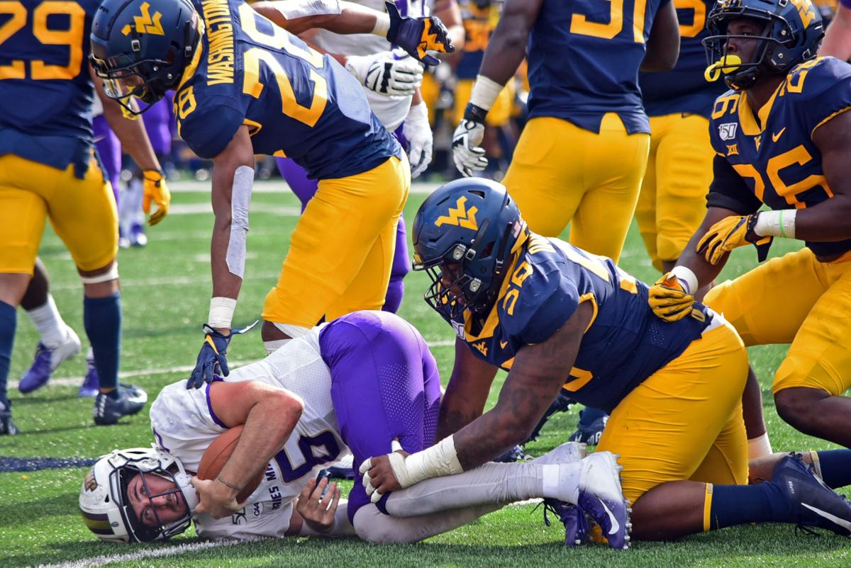 West Virginia linebacker Jared Bartlett tackles James Madison quarterback Ben DiNucci.