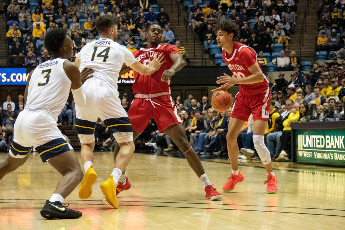 WVU's Chase Harler (14) and Gabe Osabouhien defend the basket against Boston's Javante McCoy.