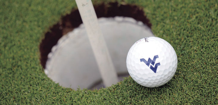 A WVU golf ball about to go in the hole.
