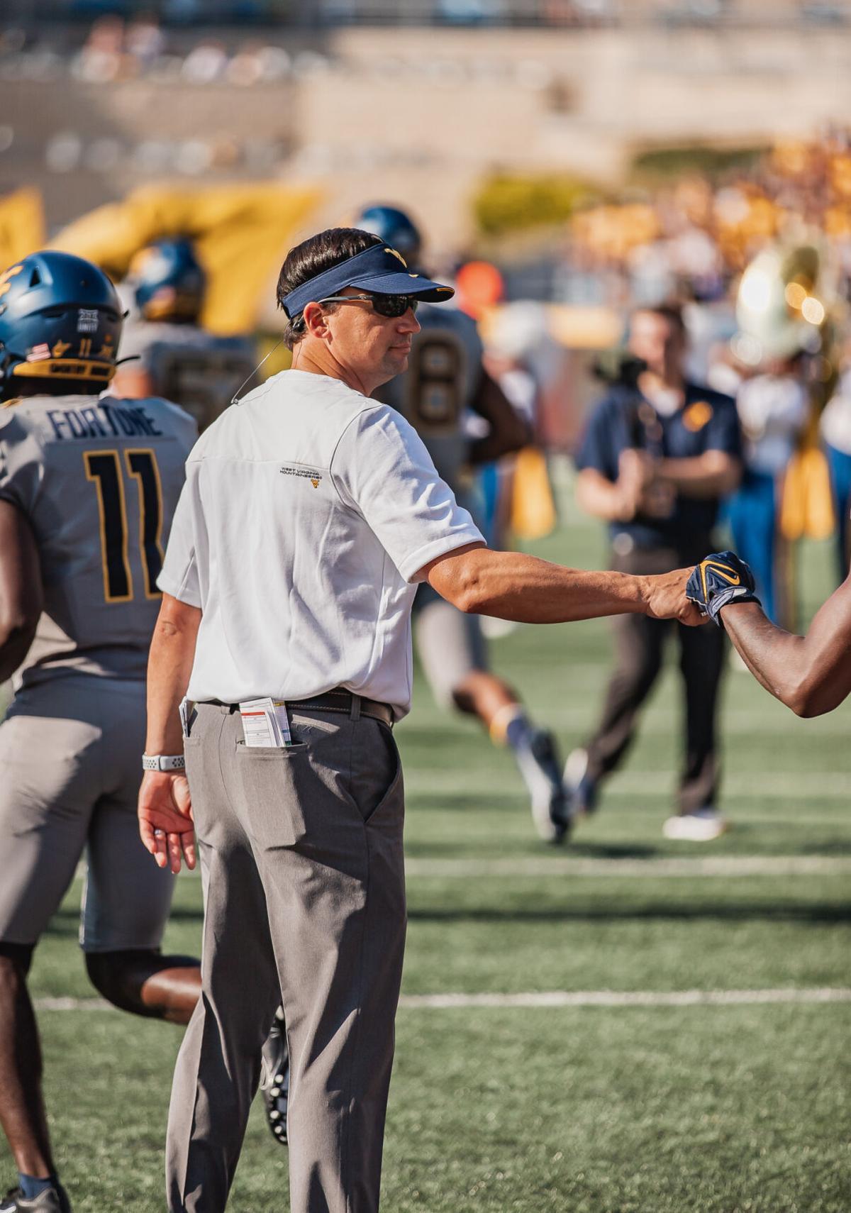 West Virginia head coach Neal Brown walks on the field prior to kickoff against Long Island at Milan Puskar Stadium in Morgantown, W.Va., on Sept. 11, 2021.