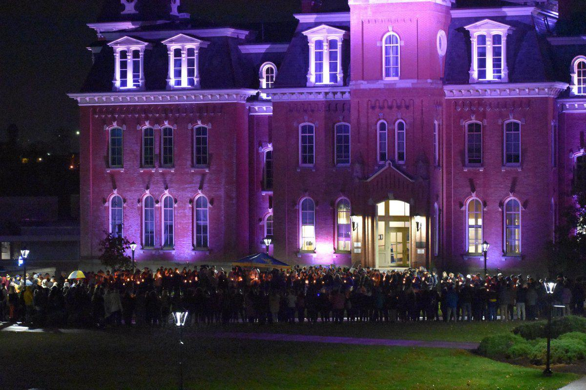 David Rusko, an SAE brother currently hospitalized, stand in front of Woodburn Hall with candles on the night of Nov. 12, 2018