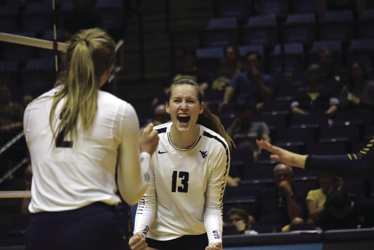 Natania Levak celebrating a WVU point in volleyball.