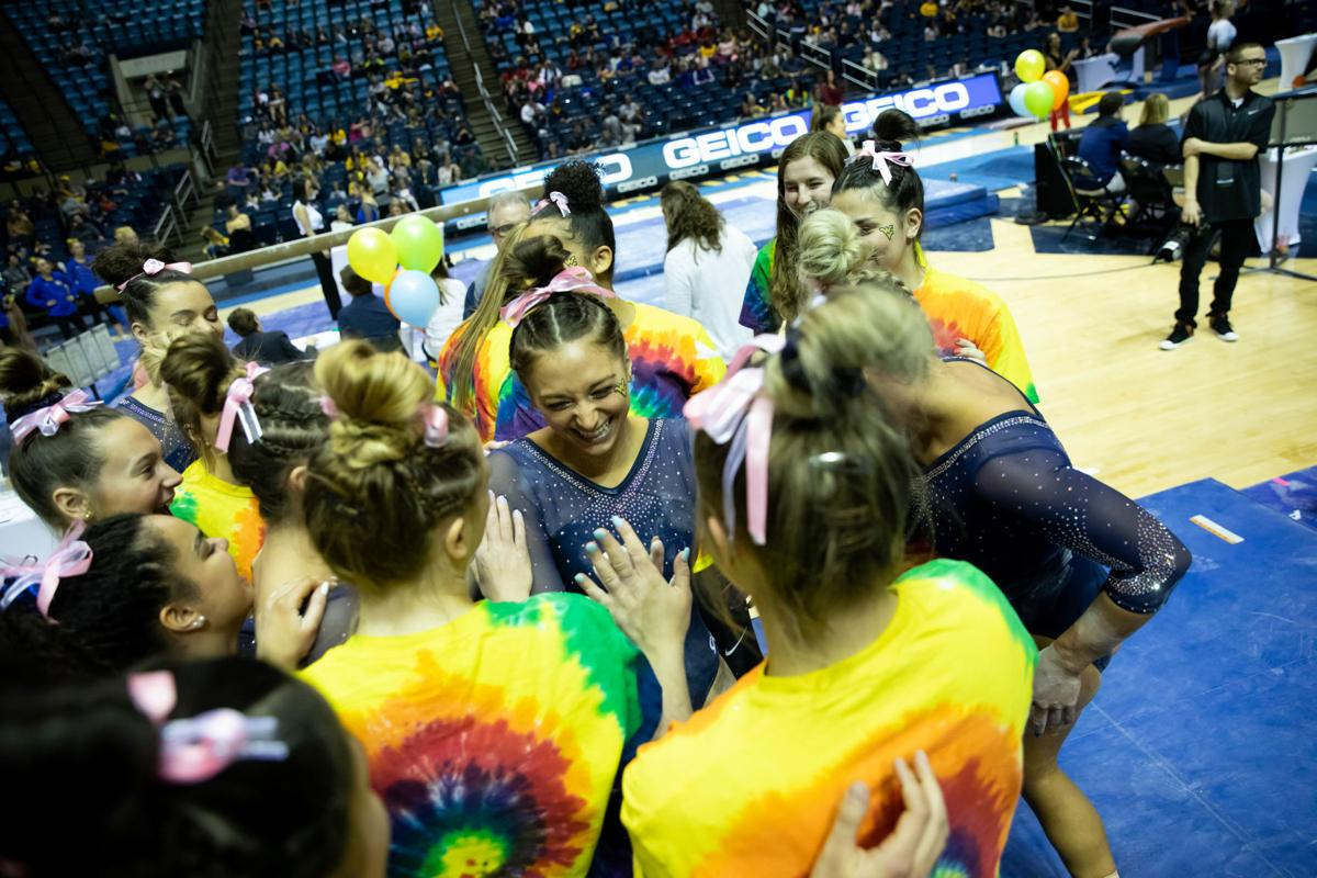 March 1, 2020. WVU Coliseum. WVU gymnastics teammates celebrate following completing their bars routines.
