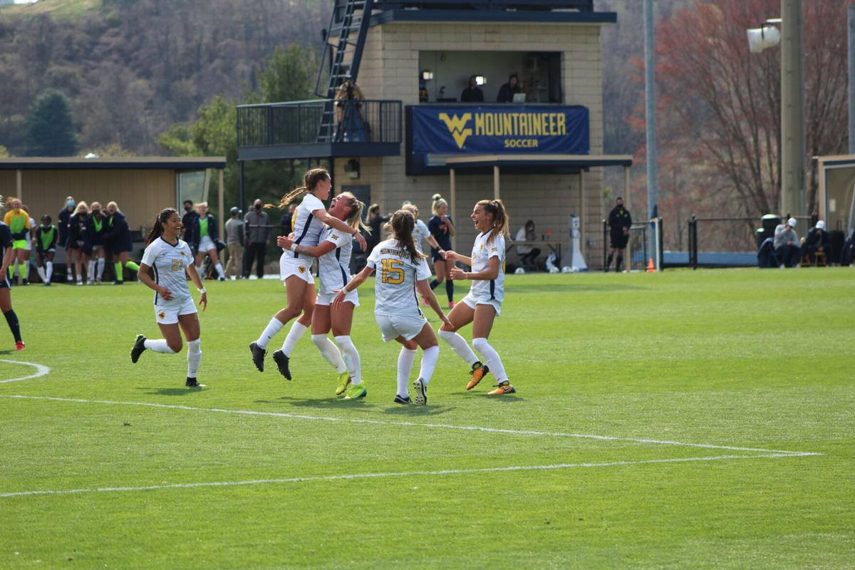 West Virginia celebrates Isabella Sibley's goal against Virginia at Dick Dlesk Soccer Stadium in Morgantown, W.Va., on April 3, 2021.