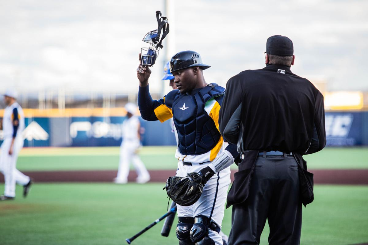 Paul McIntosh taking off his catchers mask during a game versus Kansas at the Monongalia County Ballpark in Morgantown, W.Va., on March 26 2021.