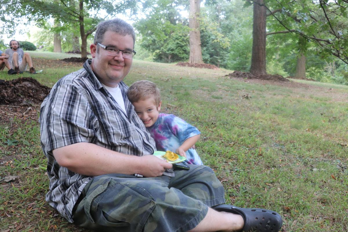Michael Ginsburg and his son Tucker enjoy a fresh pawpaw at the Pawpaw Party on Sept. 12.