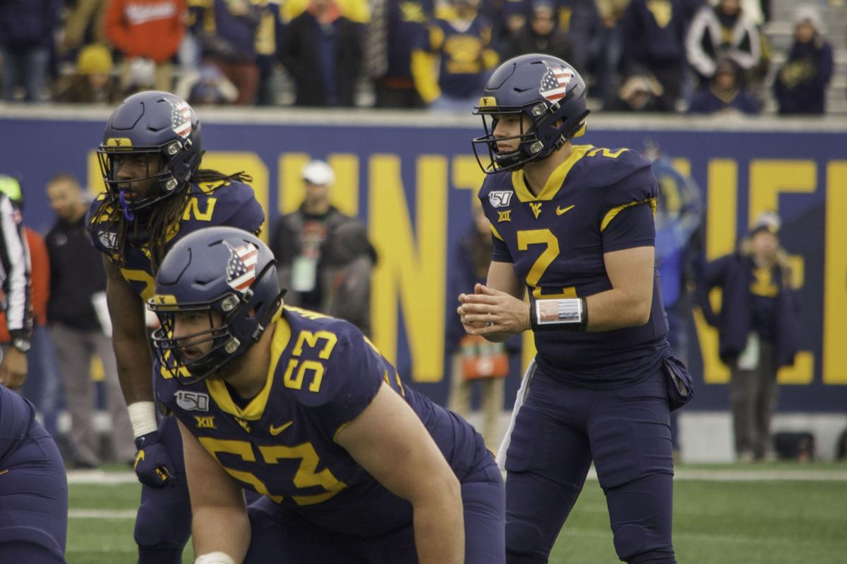 WVU Quarterback Jarret Doege prepares for the snap on the play.