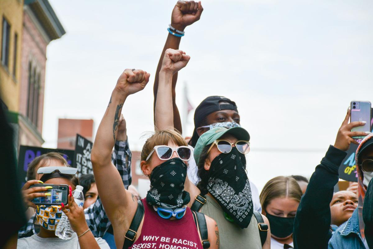 Jun. 2, 2020 - A group of protesters raise their fists together in downtown Morgantown.