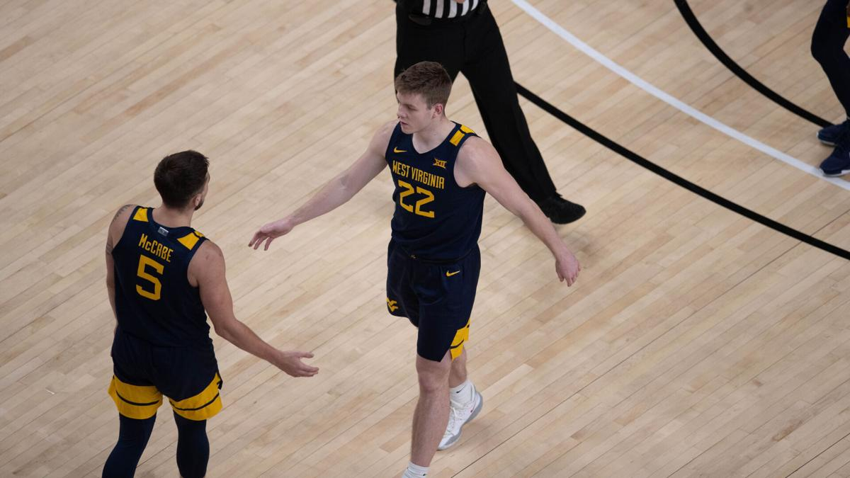 West Virginia guards Sean McNeil (22) and Jordan McCabe (5) converse during West Virginia's game against Texas Tech in Lubbock, Texas, on Feb. 9, 2021.