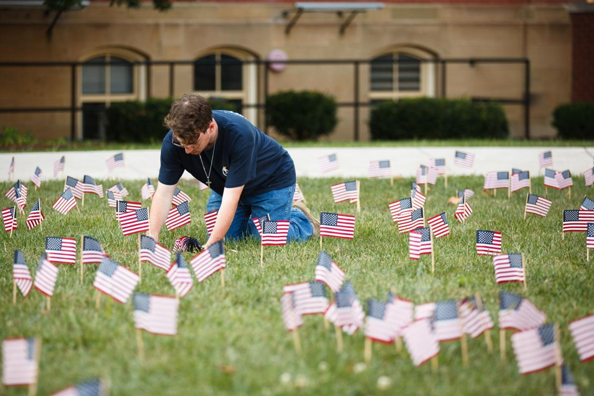 A student leaning over to plant flags into grass.