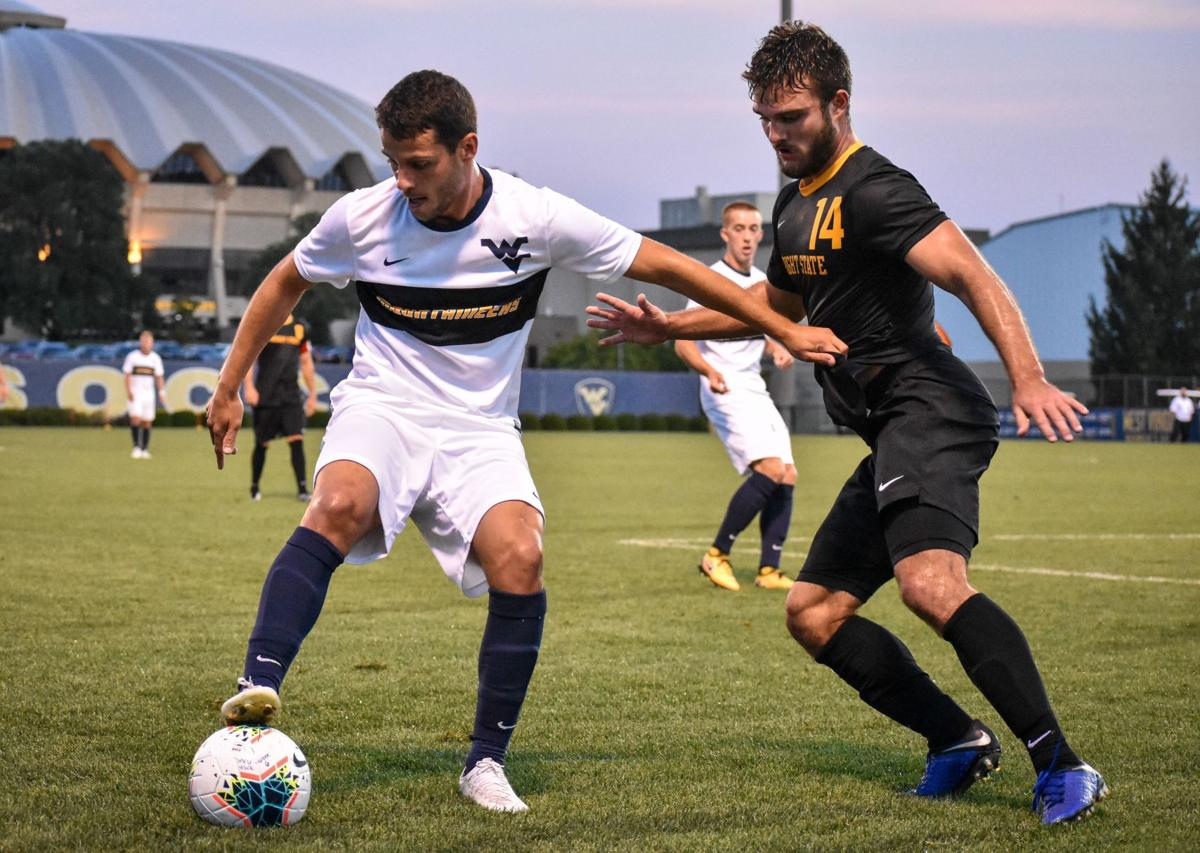 A West Virginia men's soccer player attempts to keep the ball away from a Wright State player.