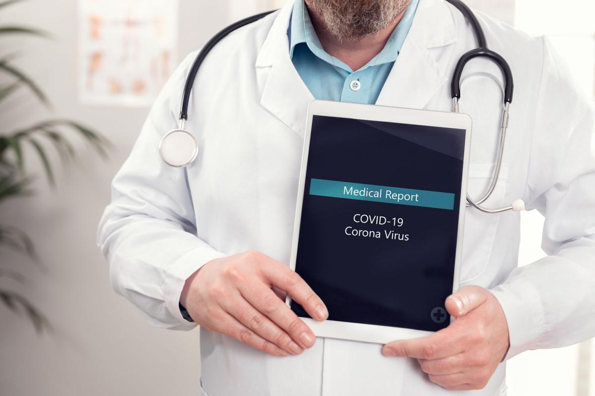 Male doctor showing medical covid-19 coronavirus report on a tablet