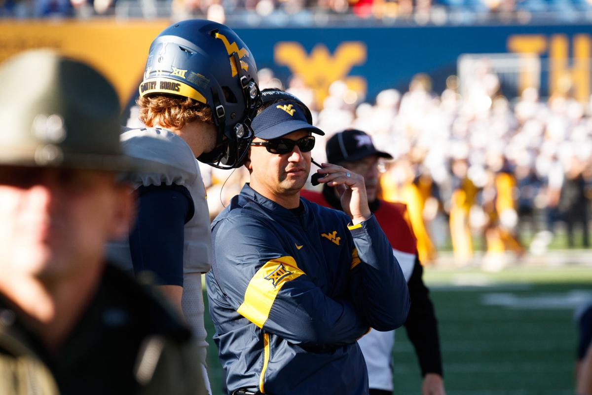 West Virginia head coach Neal Brown talks to Jack Allison prior to him replacing the injured Austin Kendall at quarterback.