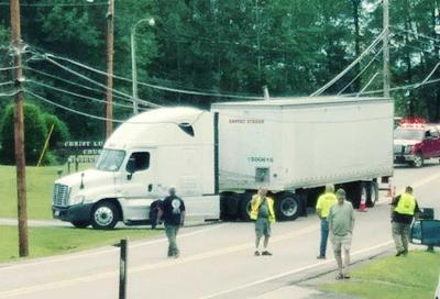 Tractor-trailer gets caught on lines