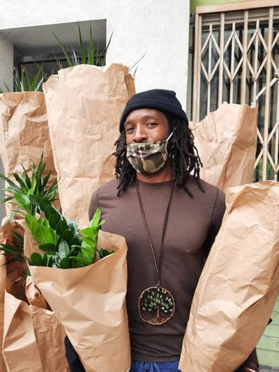 Louis Easton poses with wrapped plants before they are delivered