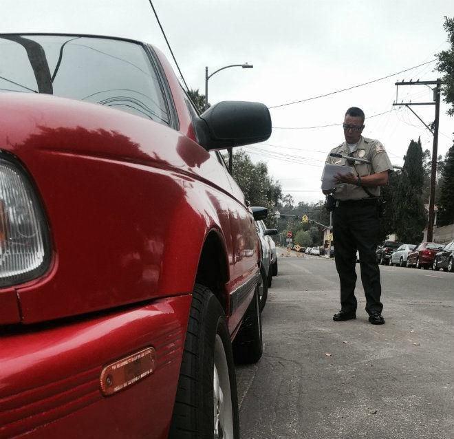 Parking enforcement officer writing a ticket