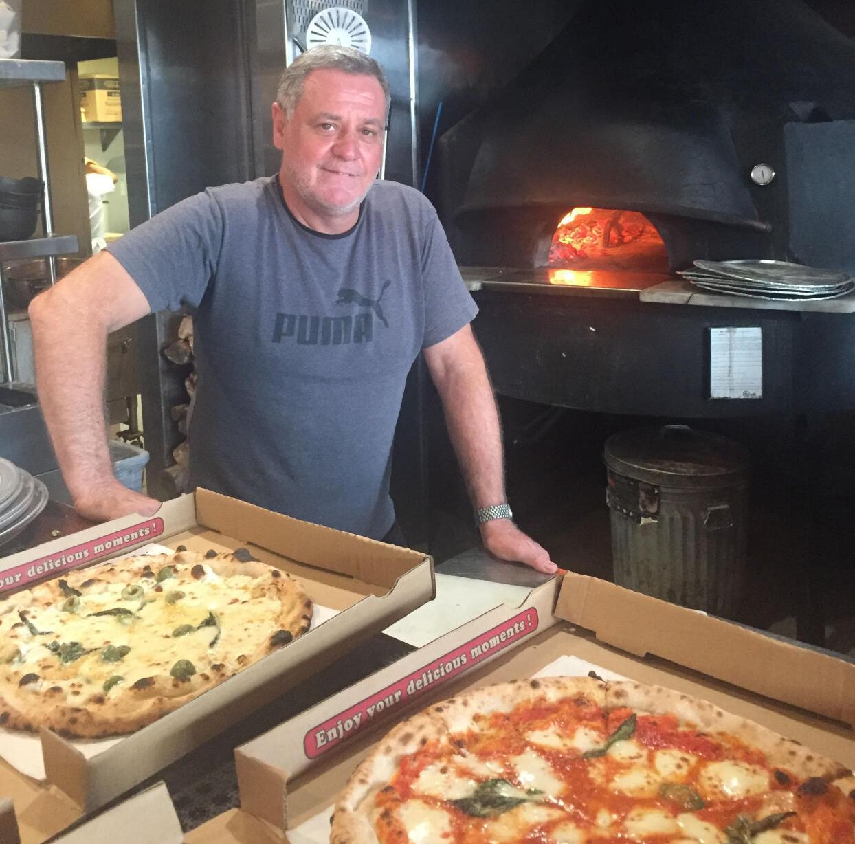Claudio Blotta in front of All'Acqua's firewood pizza oven