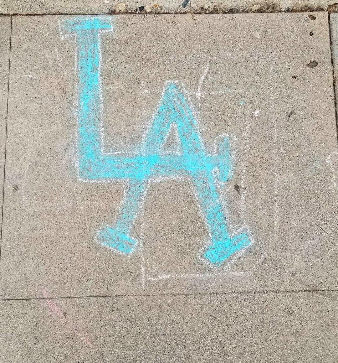 LA drawn in chalk on the sidewalk