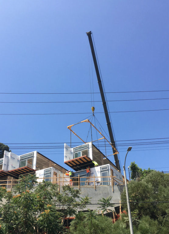 Echo Park prefab homes dropped into place; homes going up near stadium; debate continues over gas station monument