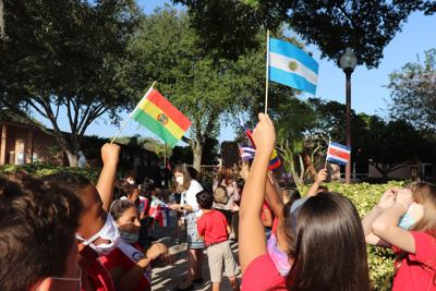 St. John Vianney Catholic School students wave flags