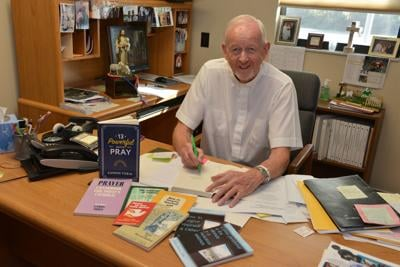 """Father Eamon Tobin, pastor of Ascension Parish Melbourne sits at his writing desk in 2017 after the release of his book, """"13 Powerful Ways to Pray"""" published by Dynamic Catholic. Father Tobin passed to eternal life Jan. 1, 2021."""
