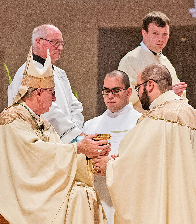 Bishop Noonan gives Father Francisco Ojeda the chalice as he hands over the bread and wine. (MARJORIE DURANTE)