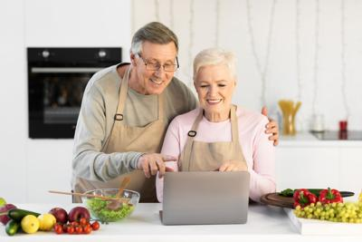 Couple Cooking And Using Laptop