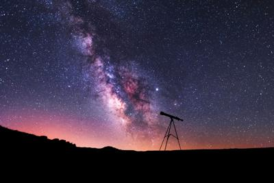 Silhouette of a telescope at the starry night and bright milky way galaxy.