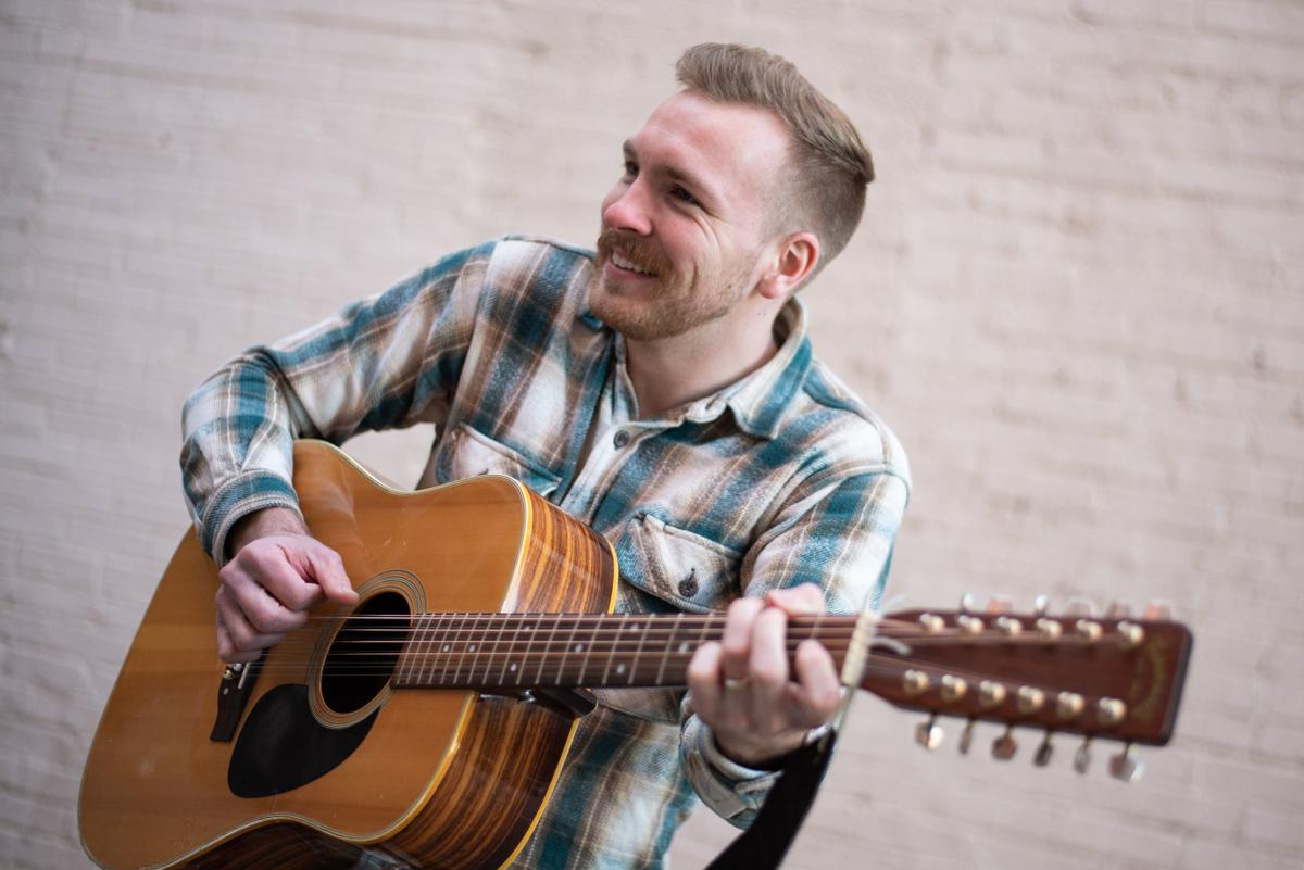 Clay Graber, acoustics and frontman of We Are the Guests, plays the guitar in an alleyway off of Poyntz Avenue on Thursday.