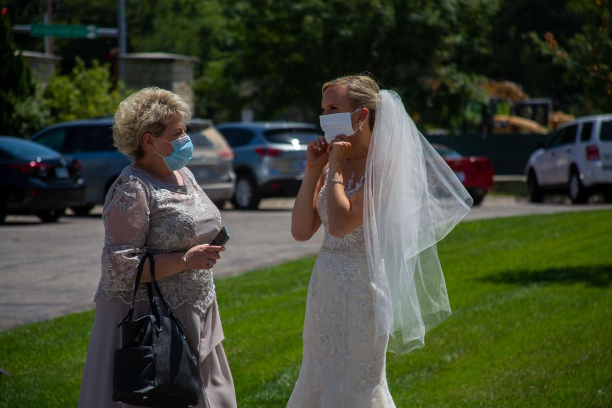 "Bride Brittany Murrell puts on mask to match dress at wedding. Brittany Murrell and Matthew Lorson held reception at the Alumni center hosting a ""drive by wedding"" where guests could say their congratulations in the safety of their cars."