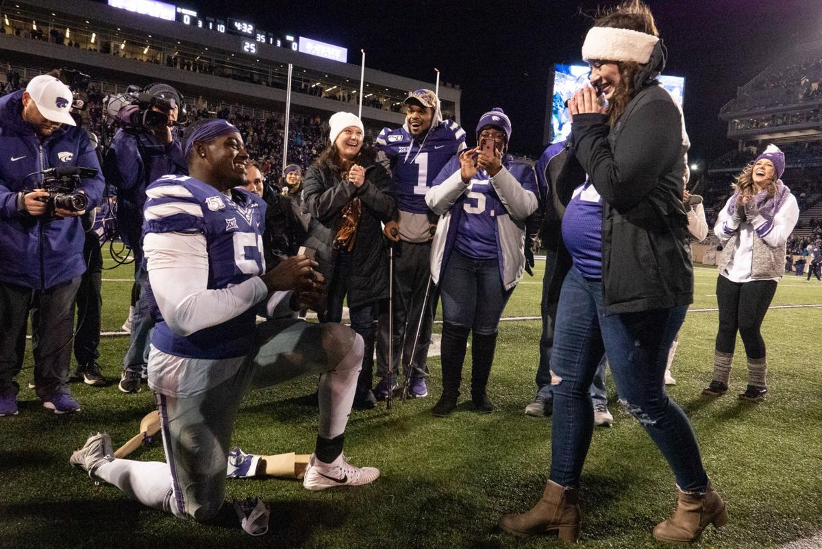 Reggie Walker (51) proposes to Calista Hickman during K-State's senior night ceremony