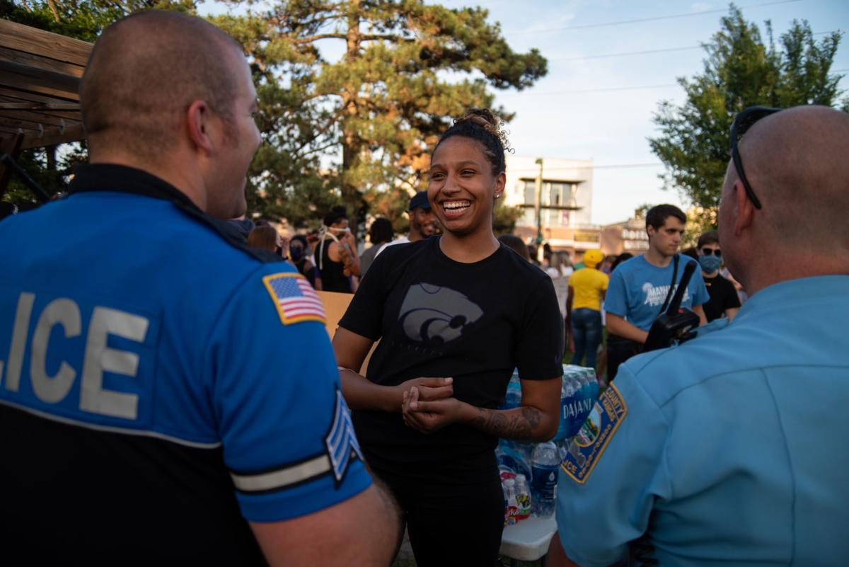 Christianna Carr talks to Sergeant Ryan Doehling, left, and Lieutenant Tim Schuck, right, at Triangle Park after the Silent and Peaceful Protest on Tuesday.