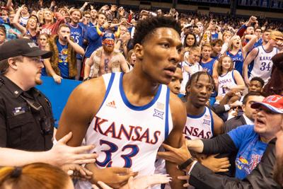 David McCormack (33) is held back by police and KU fans after getting into a fight with the K-State basketball team.