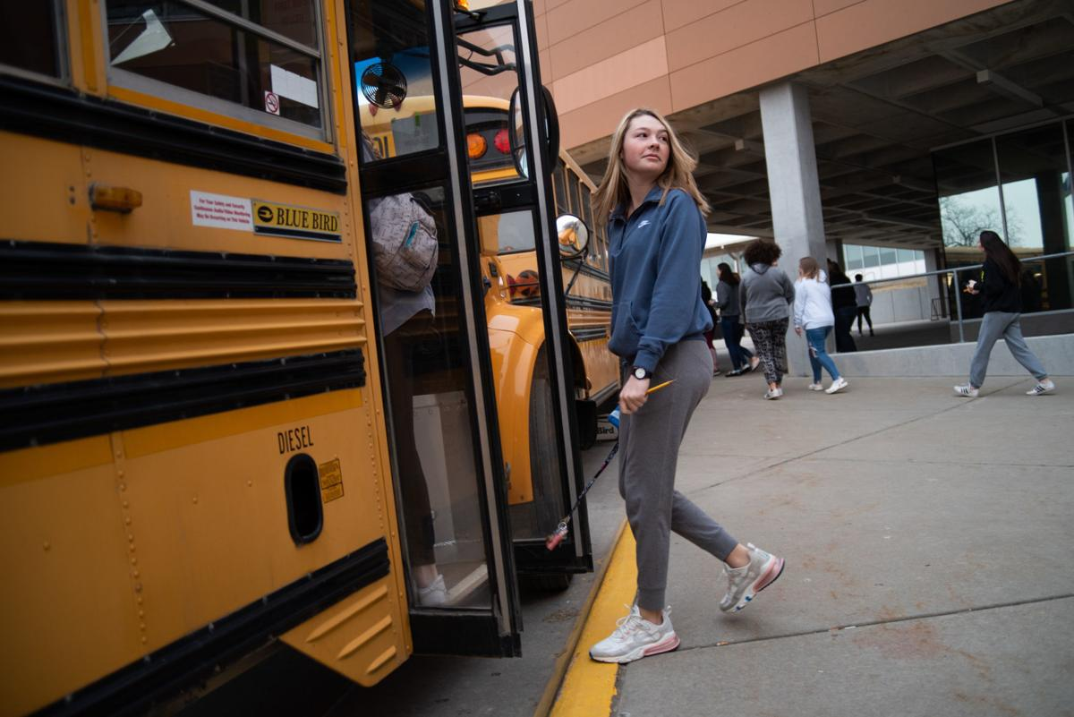 Rhys Phipps walks onto a bus outside of Manhattan High that will take her and other students to an ACT testing center.