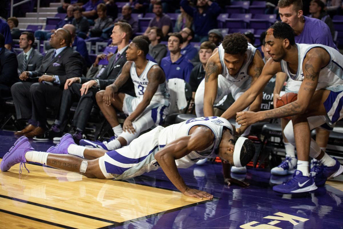 Xavier Sneed (20) lies on the ground in front of his bench after trying to dive for Cartier DiarraÕs pass that went out of bounds with under a minute left on the clock.