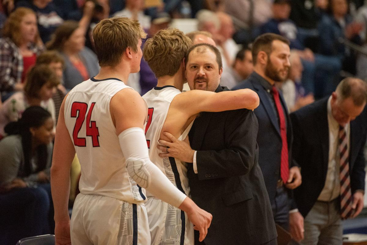 Manhattan head coach Benji George hugs Owen Braxmeyer as the time runs out on the clock.